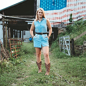 Girl in Western boots standing in front of barn with American Flag