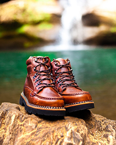 Brown boots sitting on rock in front of waterfall at Hocking Hills State Park