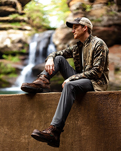 Guy sitting on wall in front of waterfall wearing brown boots and camo jacket